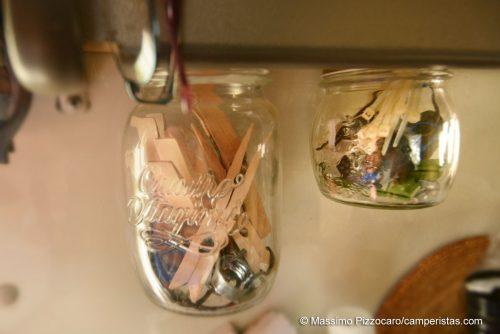 Vasetti per piccoli oggetti, avvitati alla mensola di legno.